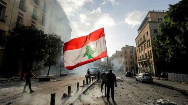 Un-protestataire-a-Beyrouth-brandit-le-drapeau-national-libanais-devant-les-forces-de-securite-pendant-une-manifestation-le-8-aout-apres-lexplosion-devastatrice-du-5-aout-383262